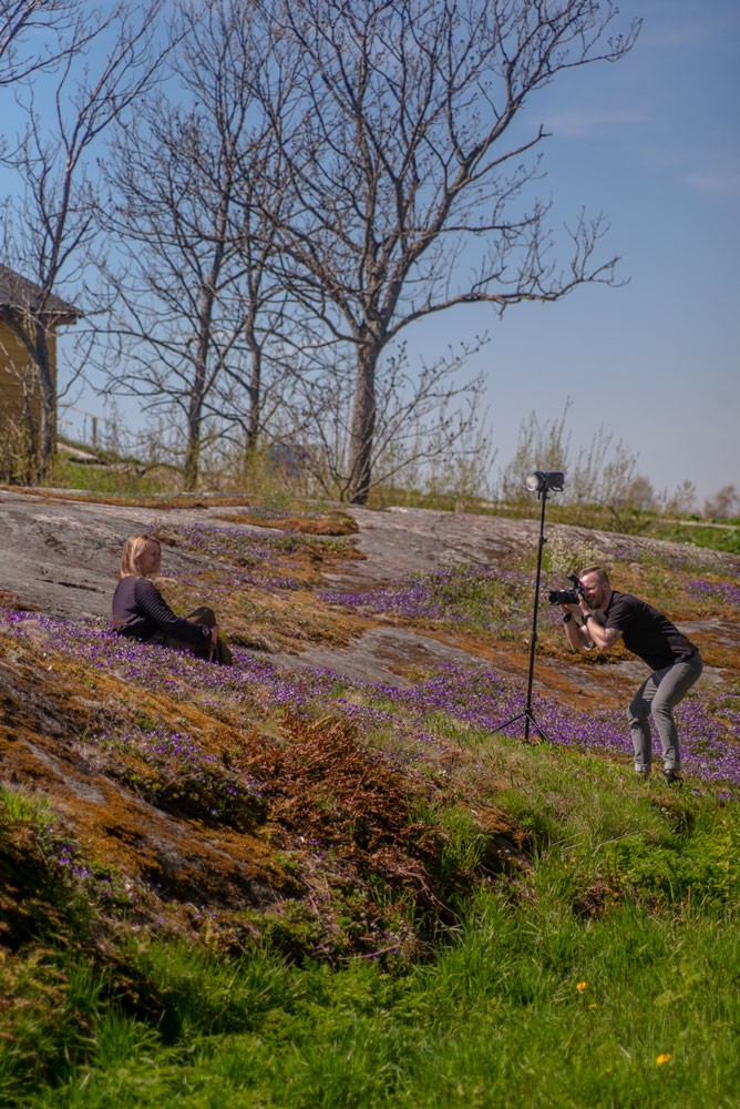 Photographer taking photos of a model in exterior settings, with falsh, in the Helsinki archipelago.