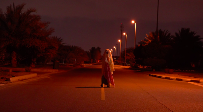 Um Al Naar walks in the middle of a street lined with orange glowing streetlights at night.