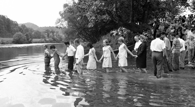 Mid-century children wade into the local river for a group baptism.
