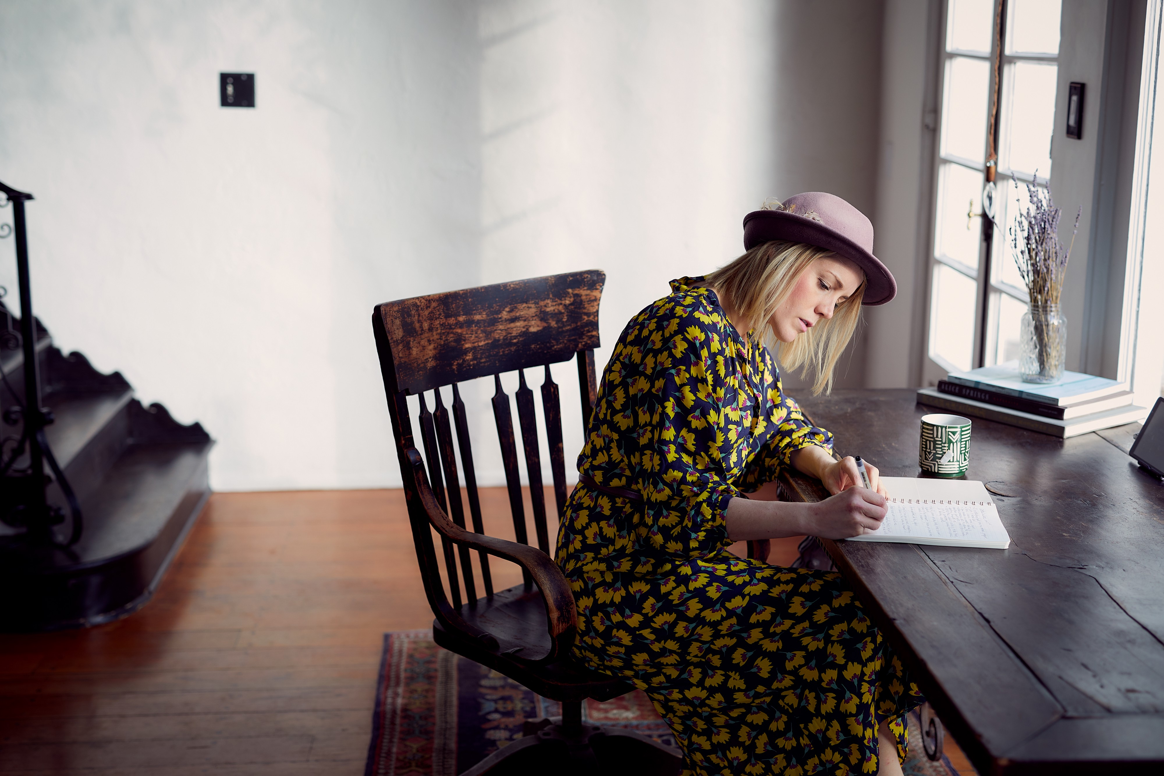Woman writing in chair by window