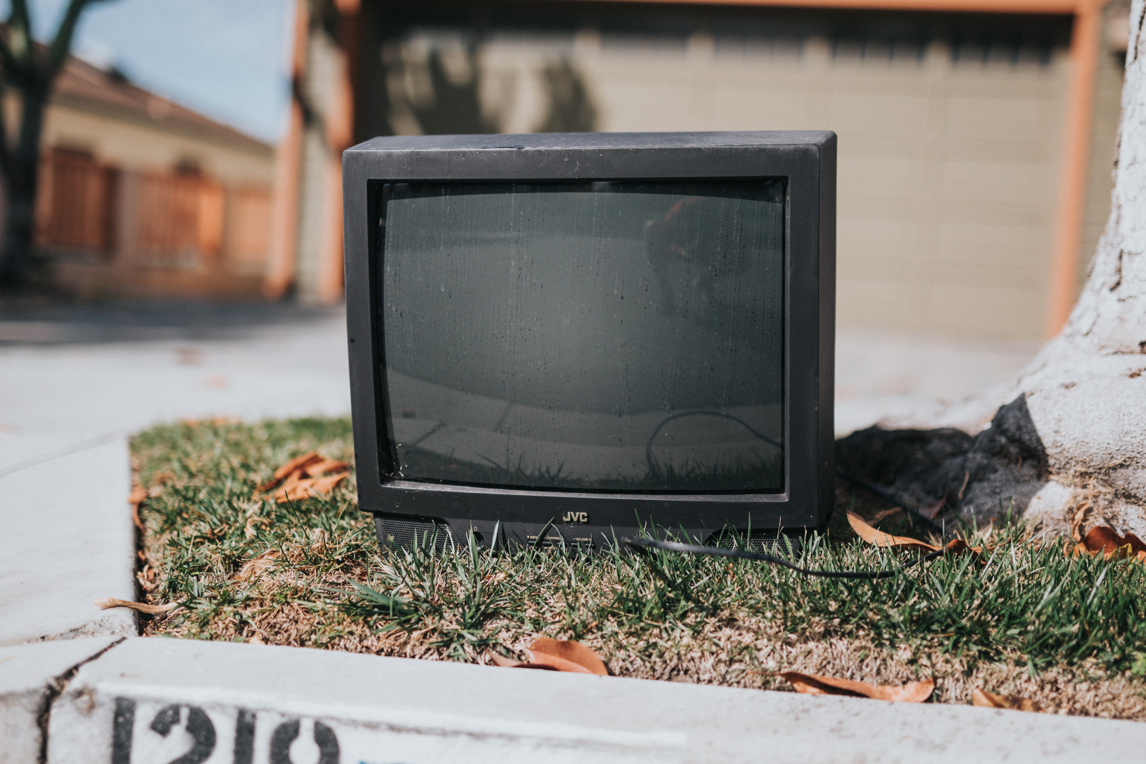 A small TV sitting on the grass on the curbside. A driveway and garage are in the background.