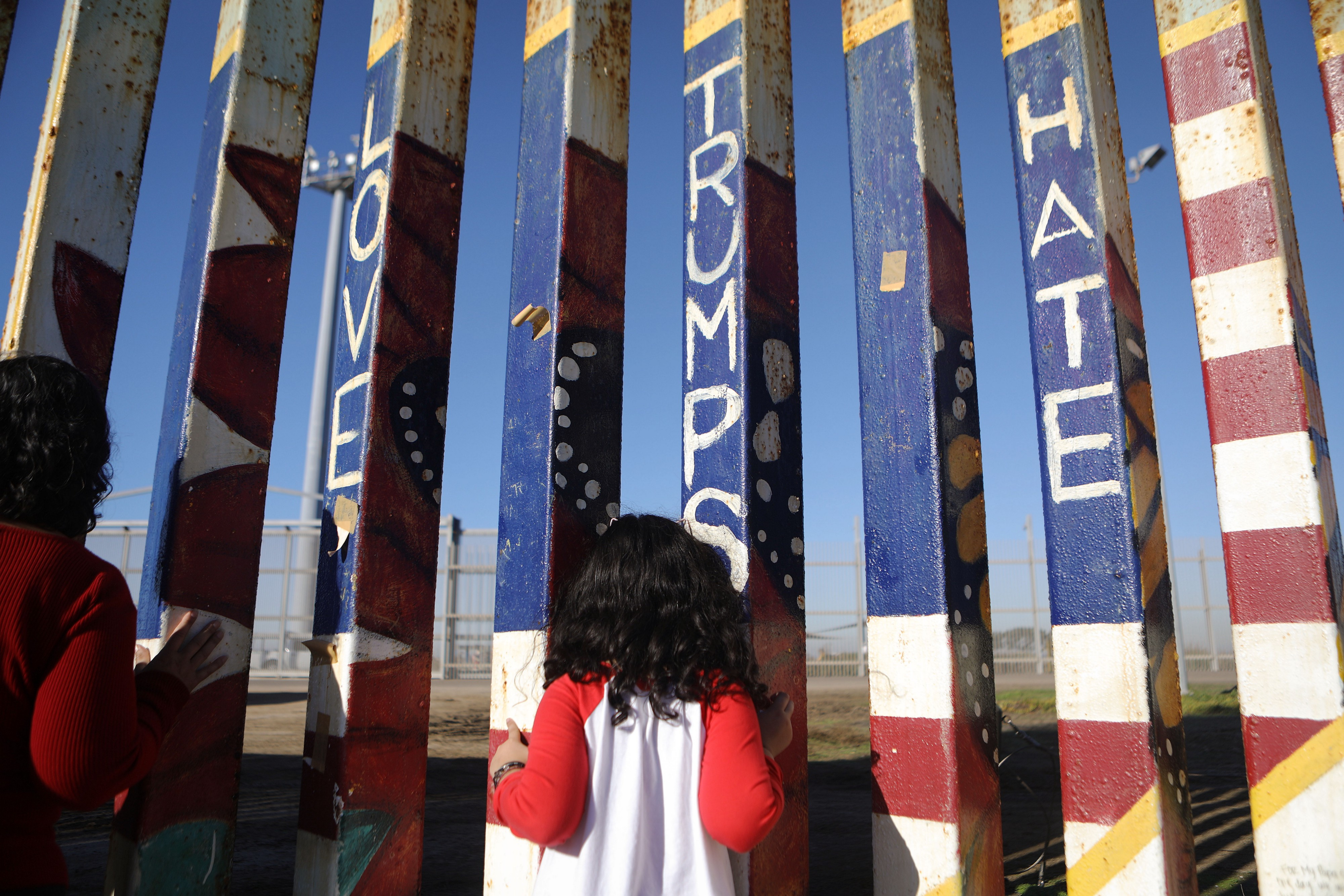 A girl stands beneath a painted message 'Love Trumps Hate' while looking towards the U.S. along the U.S.-Mexico border fence.