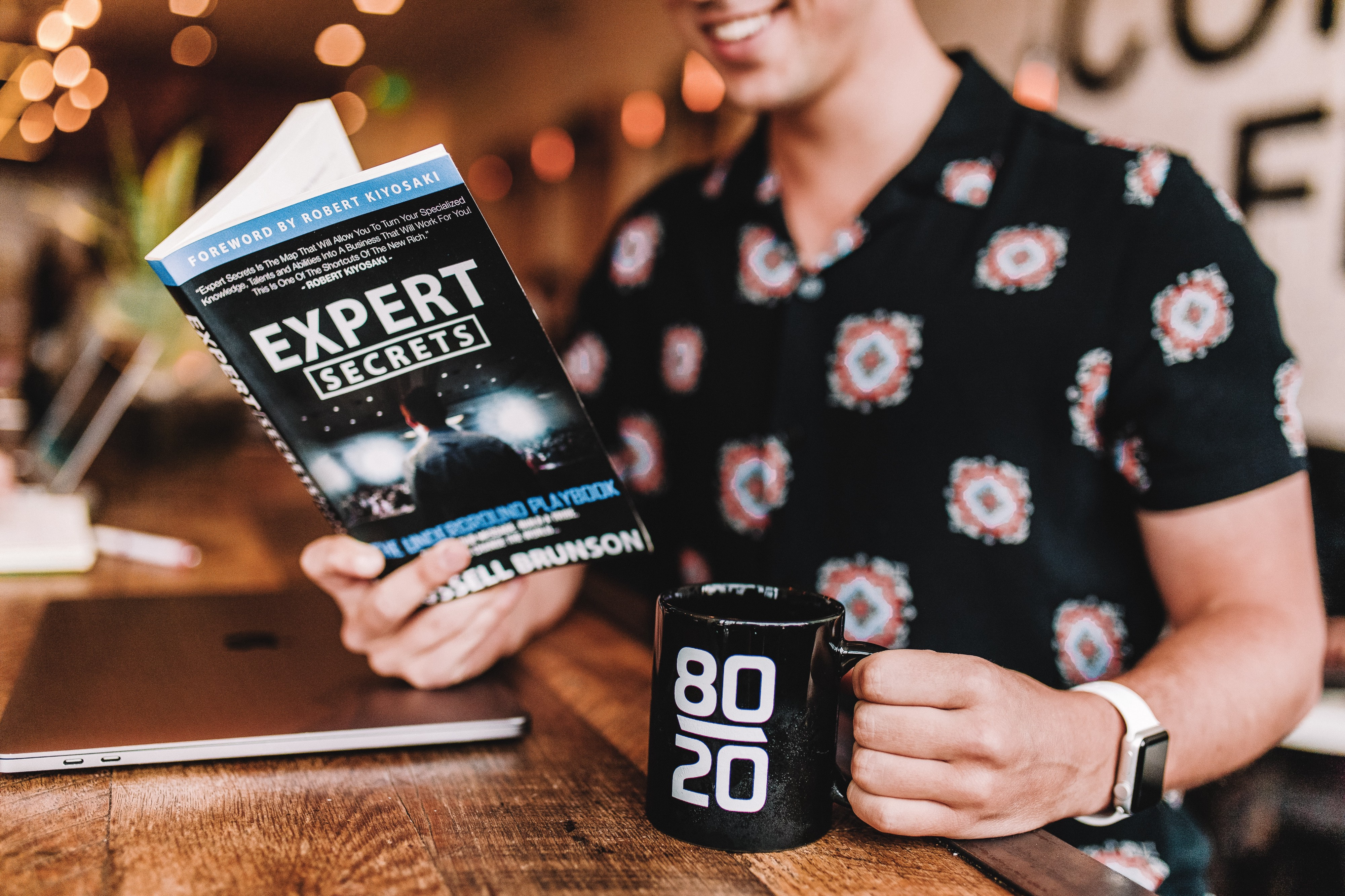 "person drinking cofee reading a book titled ""expert secrets"""