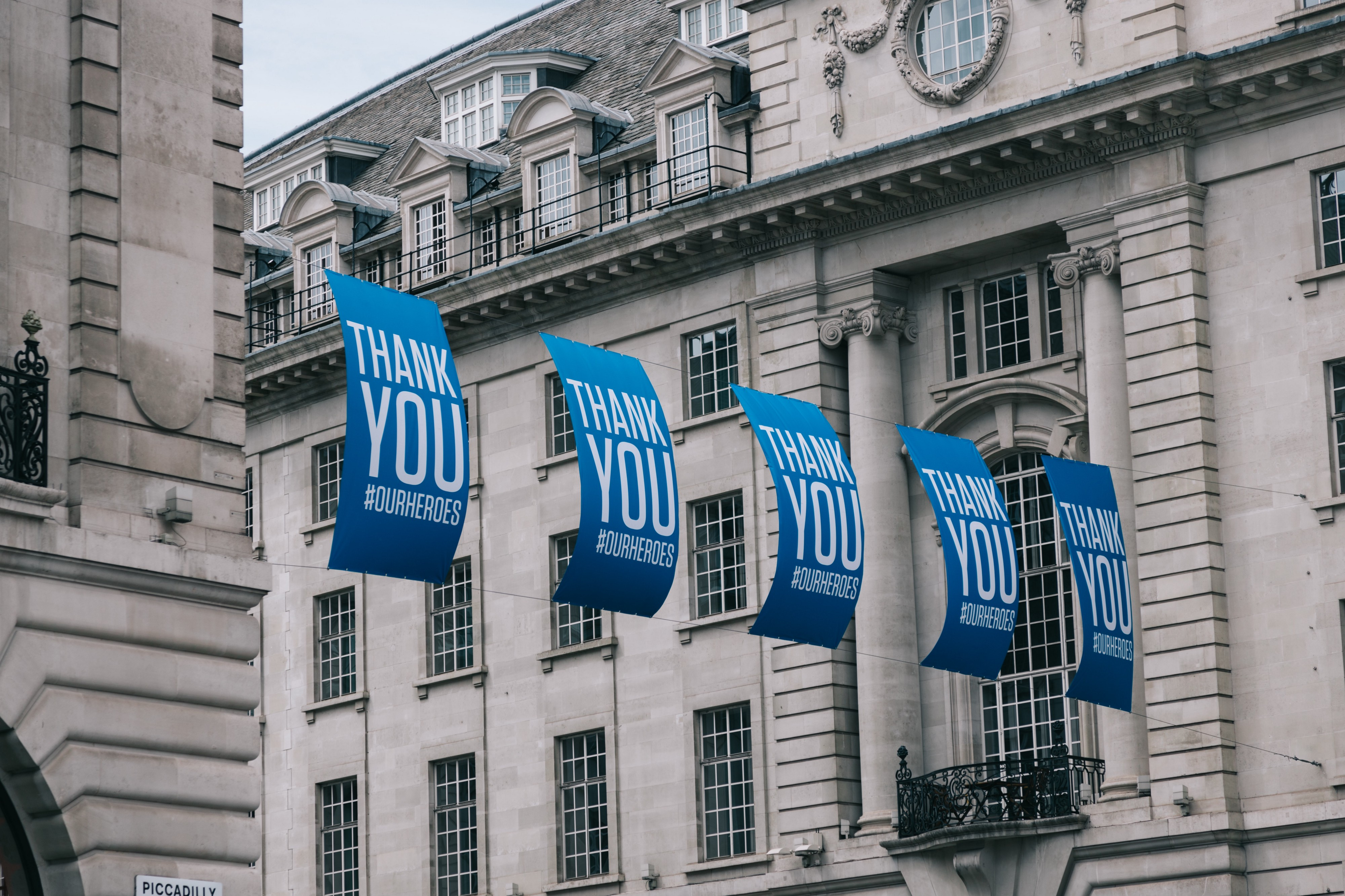 """Five large signs strung across two buildings that each say """"Thank You #OurHeroes"""""""