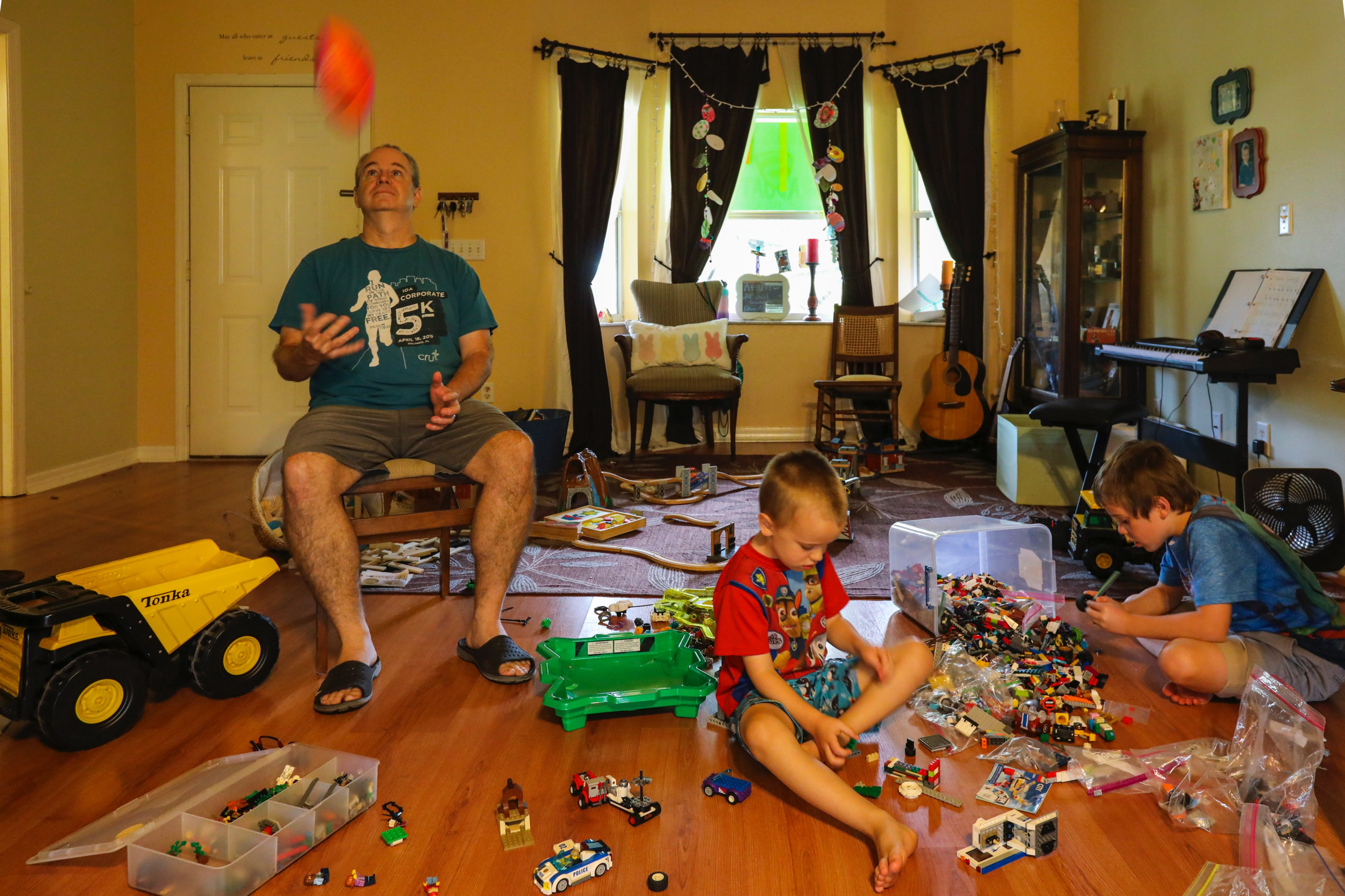 Dad and two sons playing with toys