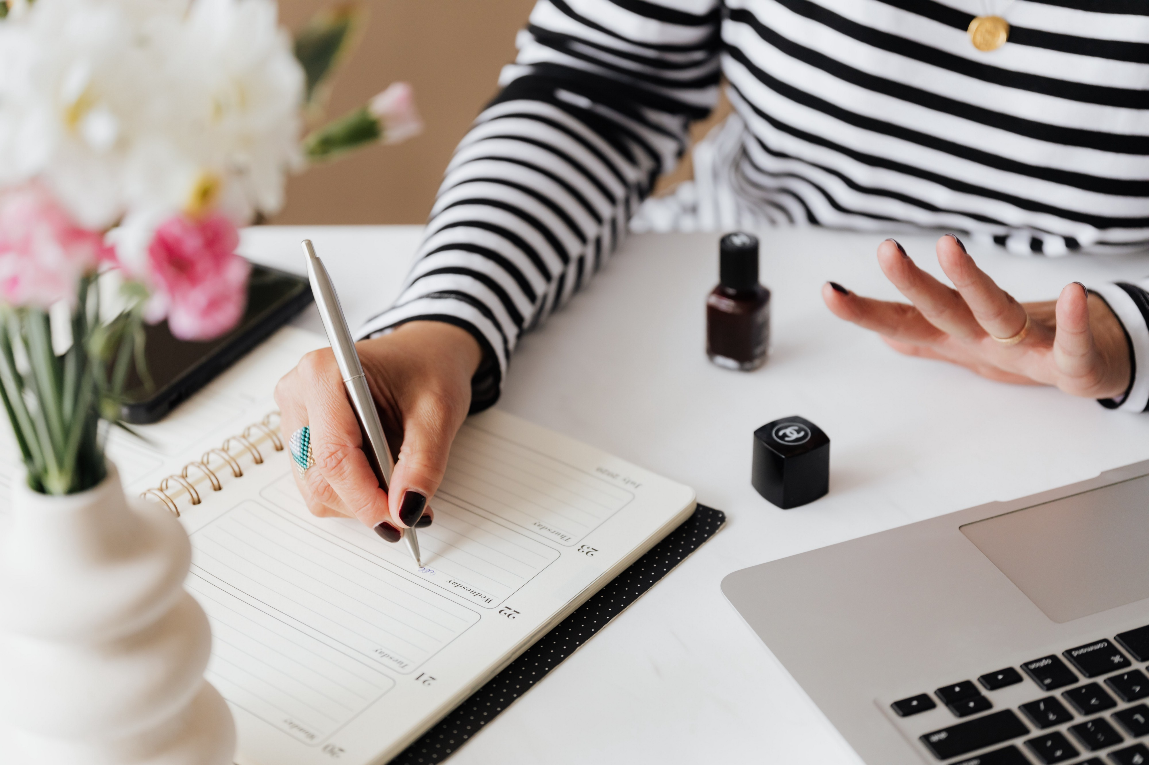 An individual writing in a planner on a neat white desk, with flowers, nail polish, and a laptop. Individual is wearing a white and black striped shirt.