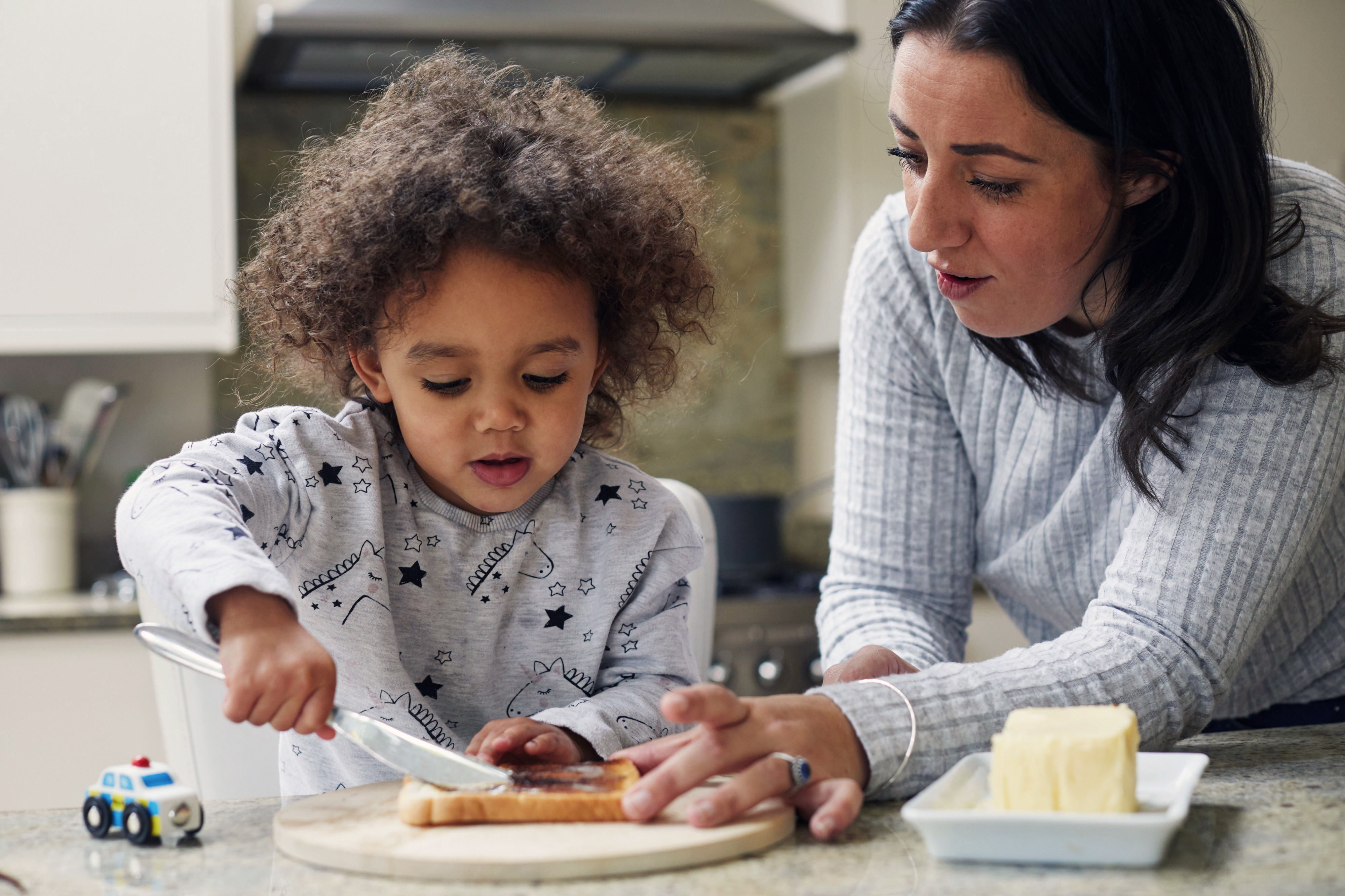 Mother and toddler daughter making a peanut butter sandwich together.