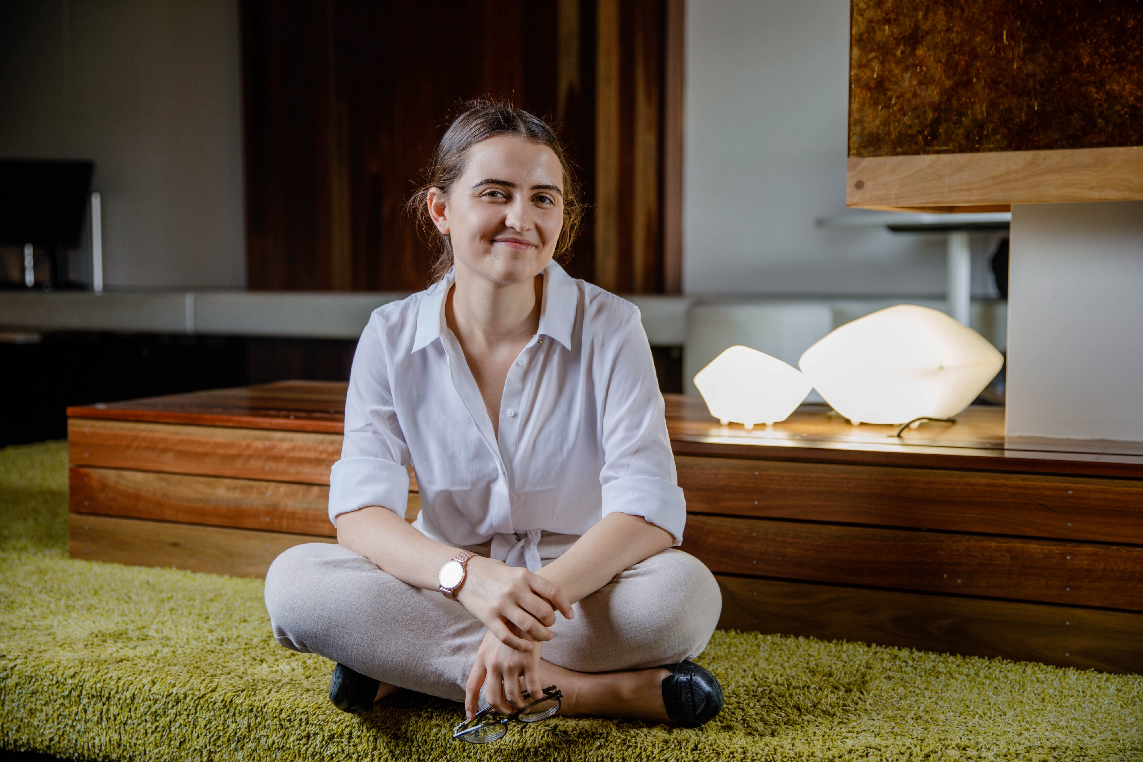 Ash Baxter, sitting cross-legged on the ground in a stylish room—plush green carpet, exposed wood and interestingly shaped lamps. She's smiling warmly at the camera, wearing a button-up shirt, trousers and loafers.