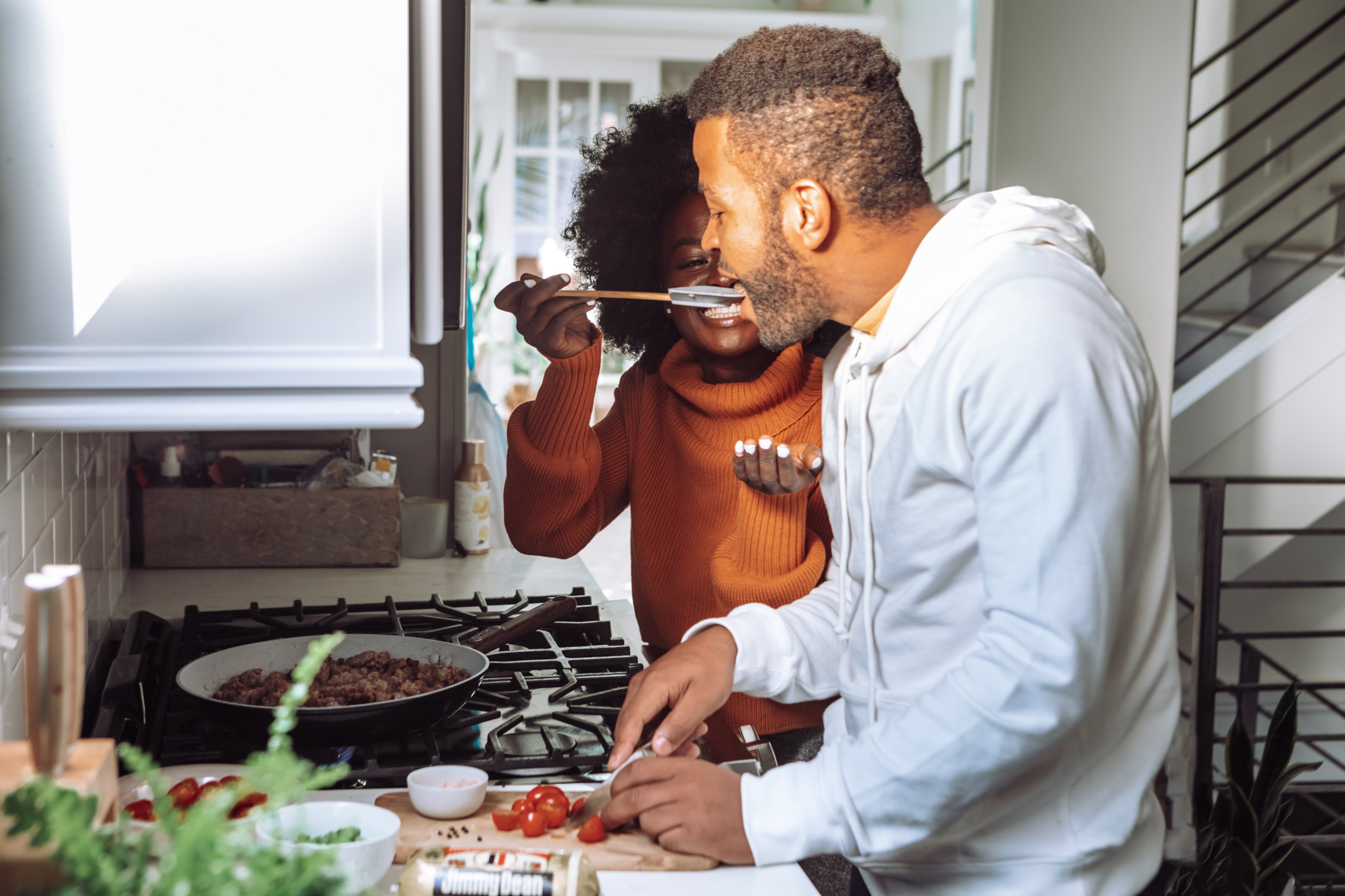 A man and woman are cooking in their kitchen, and the woman is giving him a bit of food to taste.