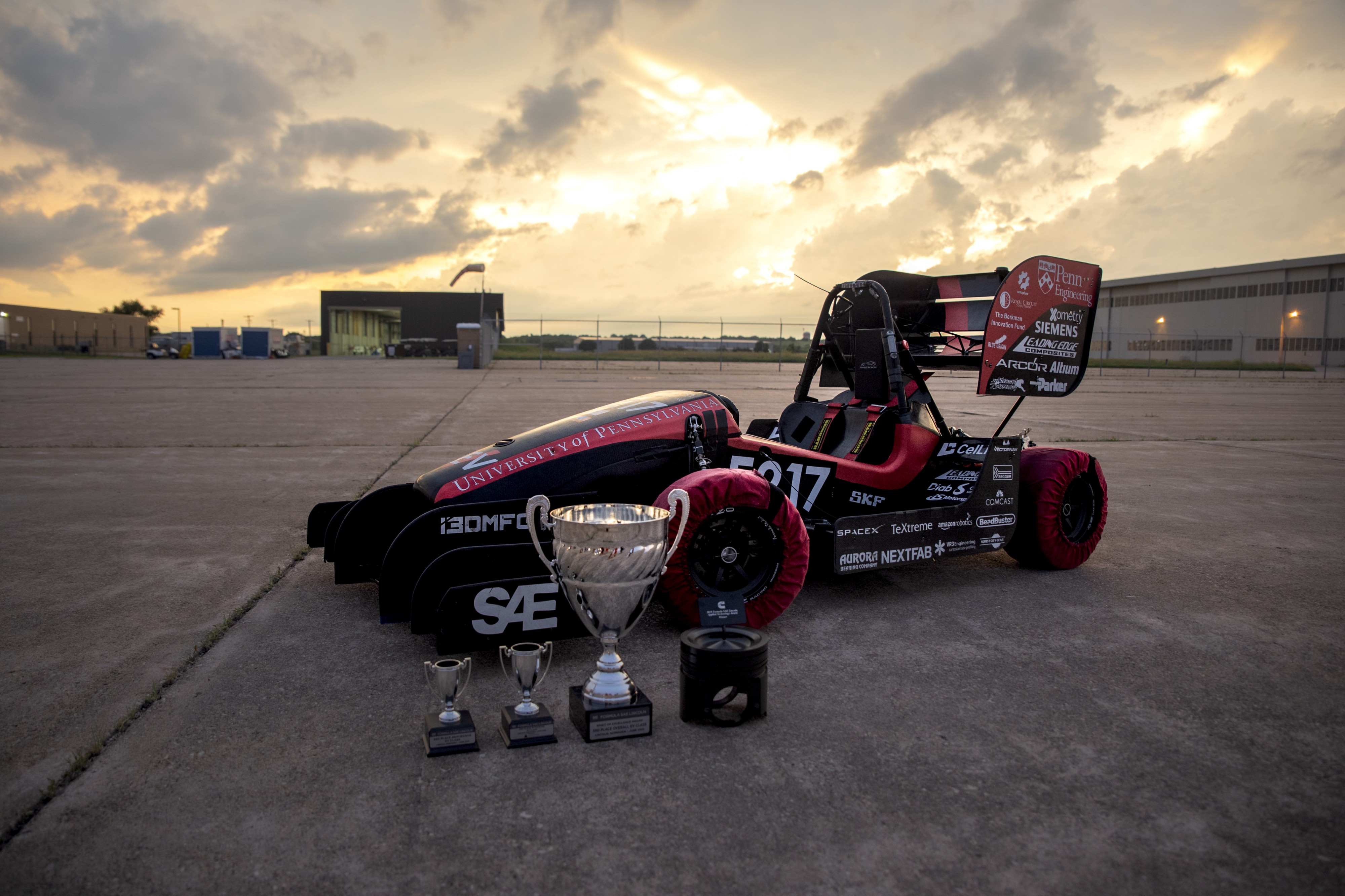 Penn Electric Racing's REV5 car photographed after the Lincoln FSAE competition, with four trophies in the foreground.