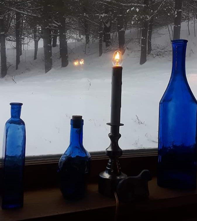 A single candle burns alongside blue glass bottles on a window sill looking out on a snowy woods.