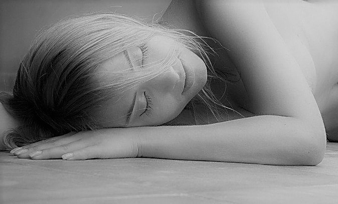 A young woman sleeps on a smooth grey floor.