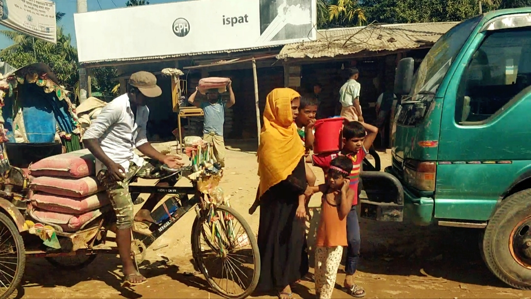 A man rides a rickshaw as a women rushes her kids along the road Cox's Bazar