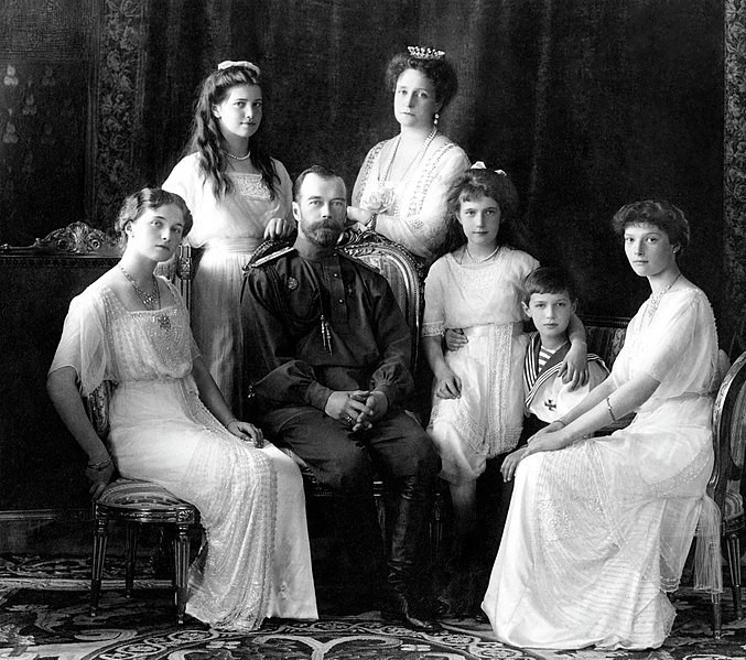Five women, a man, and a boy sit for a black and white portrait in fine clothing