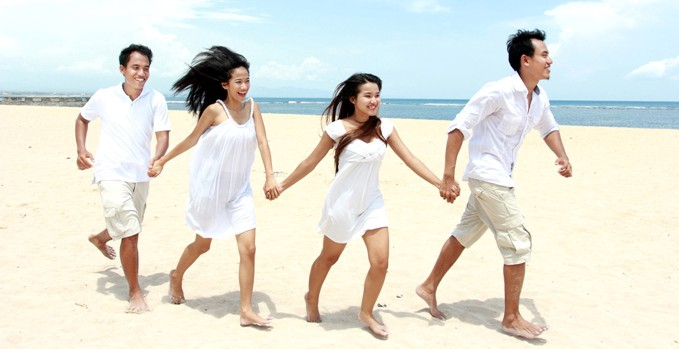 Friends running hand in hand and enjoying Beach Together