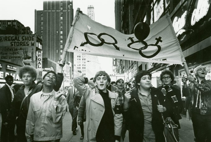 A black and white photo of a crowd of young people marching in times square, holding a banner on which there is an image of two female symbols intertwined and two male symbols intertwined. The protestors are both black and white, marching together.
