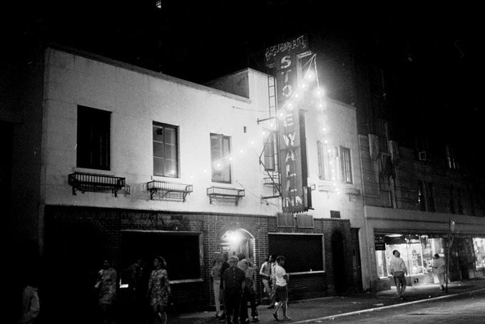 A historic photo of the Stonewall Inn, in black and white. The shopfront is lit by a neon sign that displays its name, and string lights hand outside. A few people walk the streets outside.