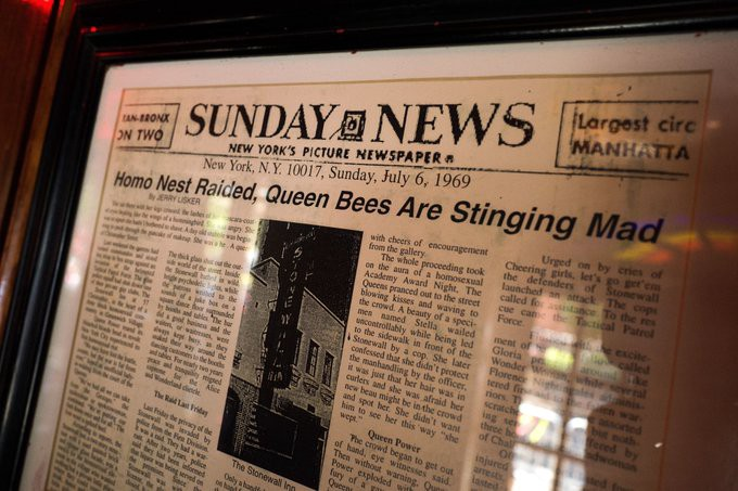 """A photograph of a newspaper in a glass case. The newspaper is from the Sunday News, and is dated Sunday, July 6th, 1969. The headline on the front page reads, """"Homo Nest Raided, Queen Bees Are Stinging Mad""""."""