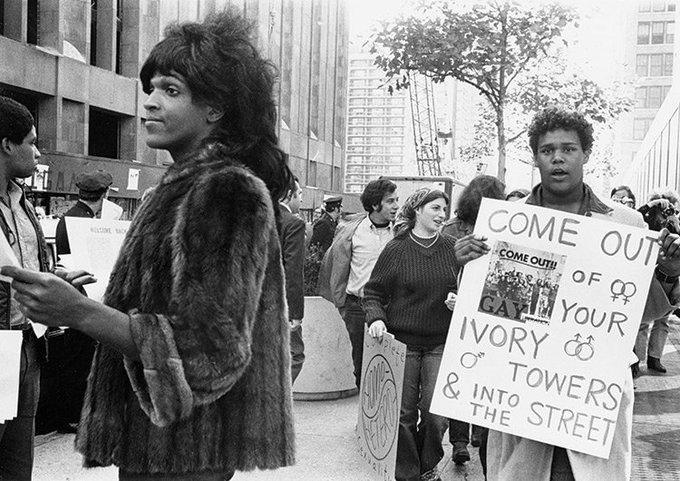 """A black and white photograph that shows Marsha P. Johnson in a fur coat passing out fliers at a peaceful protest. Behind her, other protesters hold signs. Only one is visible, and it reads, """"Come out of your ivory towers and into the streets!"""" and features two female symbols intertwined, two male symbols intertwined, and the trans symbol."""