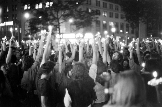 A black and white photo of a huge crowd gathered in New York City on the first anniversary of the Stonewall Riots, all holding candles aloft in rememberance.