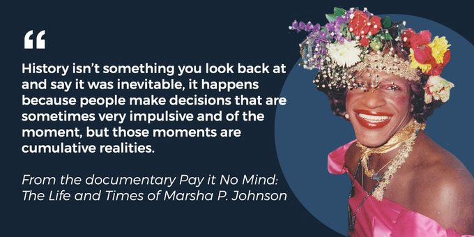 """A color photo of Marsha P. Johnson, smiling at the camera and wearing a floral crown and a pink dress. Text besides her photo reads, """"'History isn't something you look back at and say it was inevitable, it happens because people make decisions that are sometimes very impulsive and of the moment, but those moments are cumulative realities.' From the documentary Pay It No Mind: The Life and Times of Marsha P. Johnson"""""""
