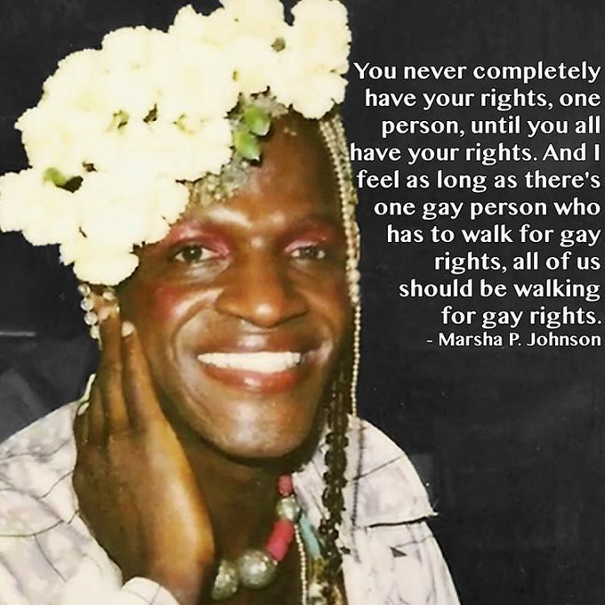 """A color photo of Marsha P. Johnson smiling at the camera. She is wearing red lipstick, pink eyeshadow, and a headpiece of white flowers. The text on this image reads, """"'You never completely have your rights, one person, until you all have your rights. And I feel as long as there's one gay person who has to walk for gay rights, all of us should be walking for gay rights.'—Marsha P. Johnson"""""""