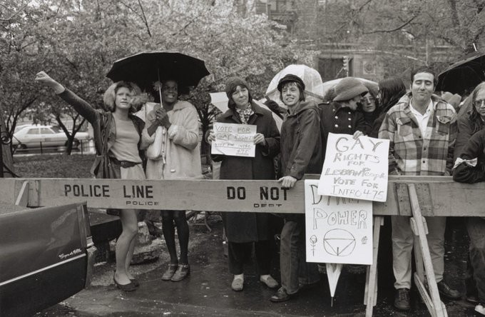 """A photo of a peaceful protest in black and white, with protesters standing under umbrellas next to a police line blockade. Sylvia Rivera and Marsha P. Johnson share an umbrella, each wearing short dresses and Marsha with a fur coat. Sylvia holds out a fist over the police line, in a symbol of resistance. Beside them are other protesters. Signs read, """"Vote for gay rights"""", """"gay rights for lesbian people"""" and """"dyke power""""."""