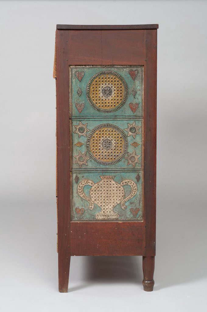Side view of a wooden pie safe featuring a panel of colorfully decorated punched tin.