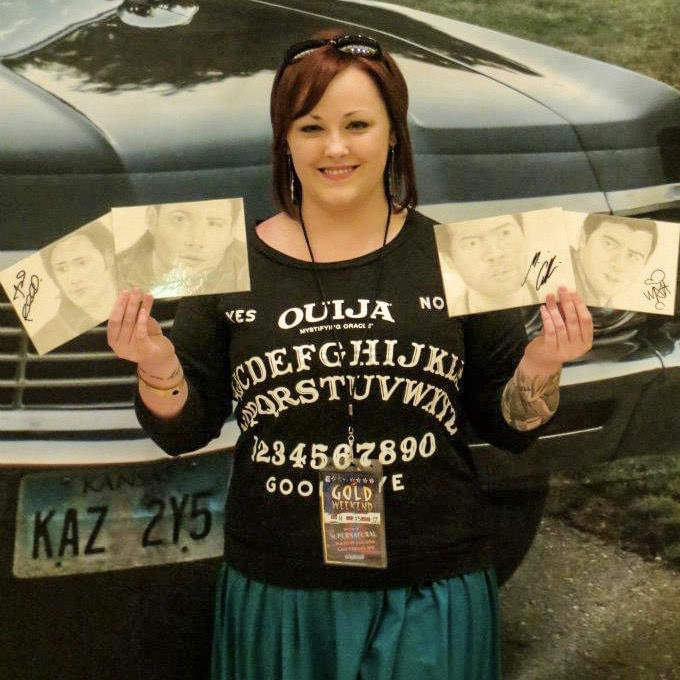 Kaela showing off her autographed fan art and posing with Baby—Sam & Dean's 1967 Chevy Impala.
