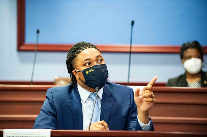 Malcolm Kenyatta sits in the chambers in Harrisburg, wearing a navy suit and a face covering, pointing and speaking as he defends access to the ballot