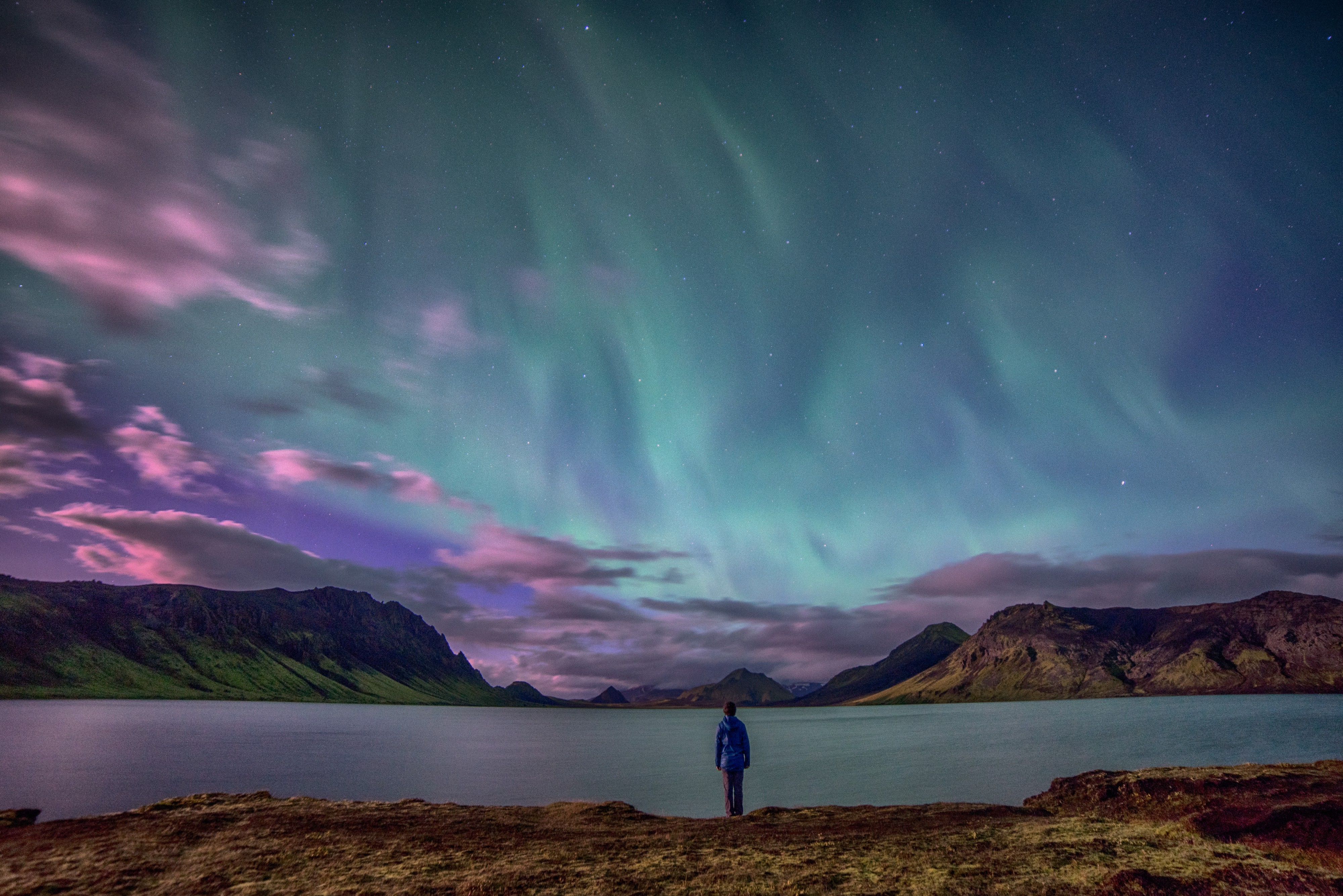 A person stands by a lake gazing at the Aurora Borealis