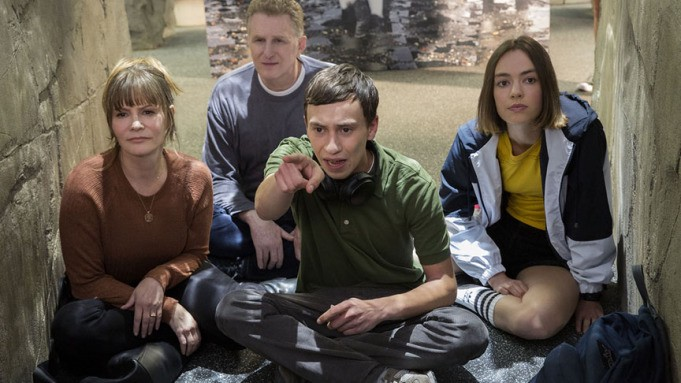 A screenshot from the show Atypical, Sam the main character sits in the centre, pointing forward, with his family around him