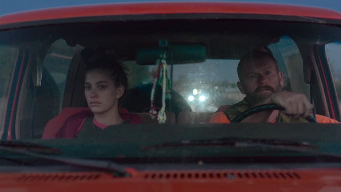 Camila Morrone (left) and James Badge Dale (right), seen tense and stone-faced through a car windshield in the film.