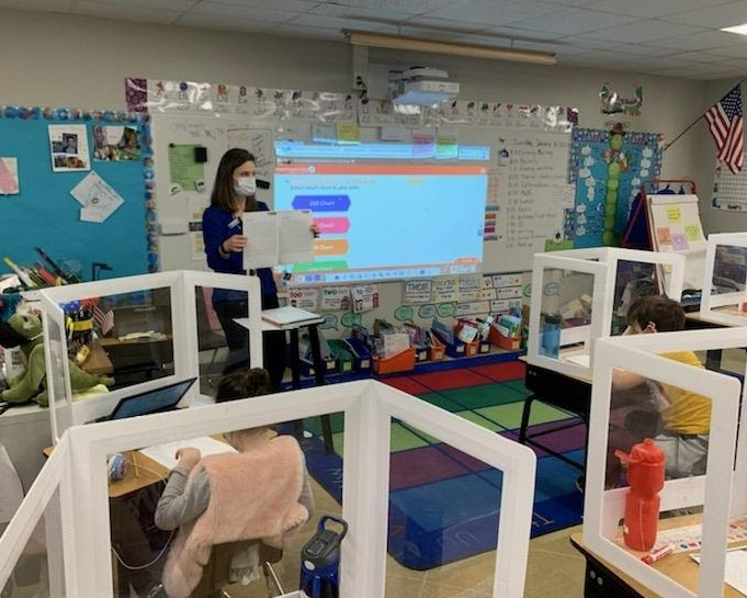 Teacher standing at the front of a classroom with a mask on teaching to students in individual cubbies at their desks.