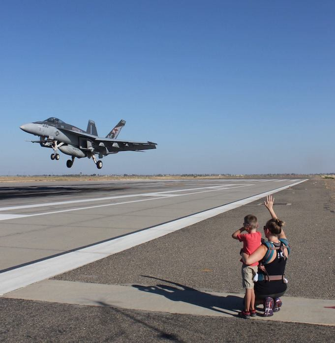 Women and young boy looking into the distance at a jet taking off