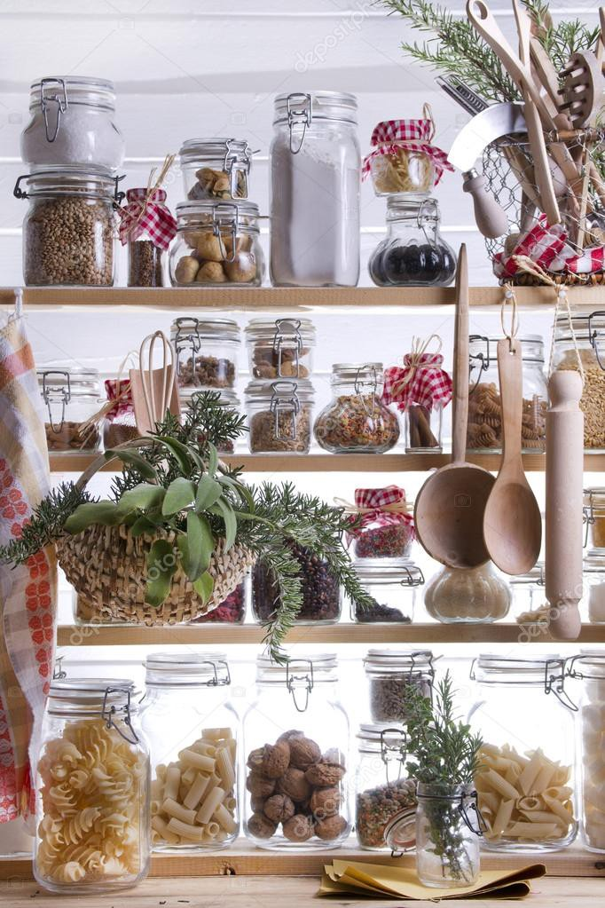A wooden frame shelving with bottles and jars of dried food, herbs, wooden spoons and a rolling pin.