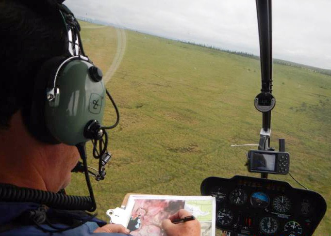a man in a helicopter flies over wetland taking notes