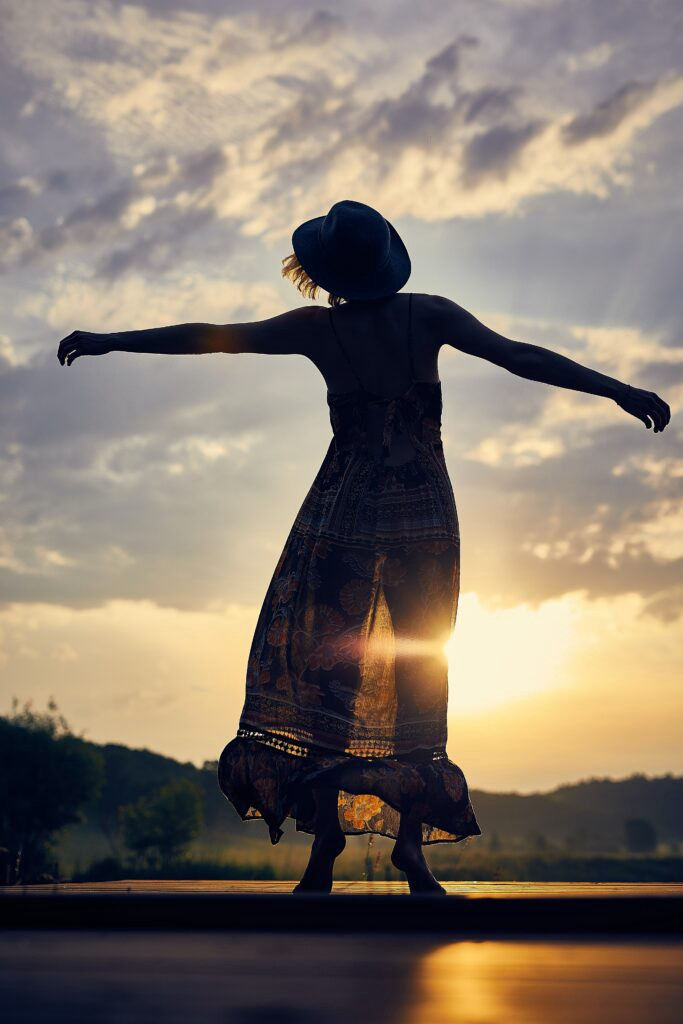 woman standing with arms to the sun