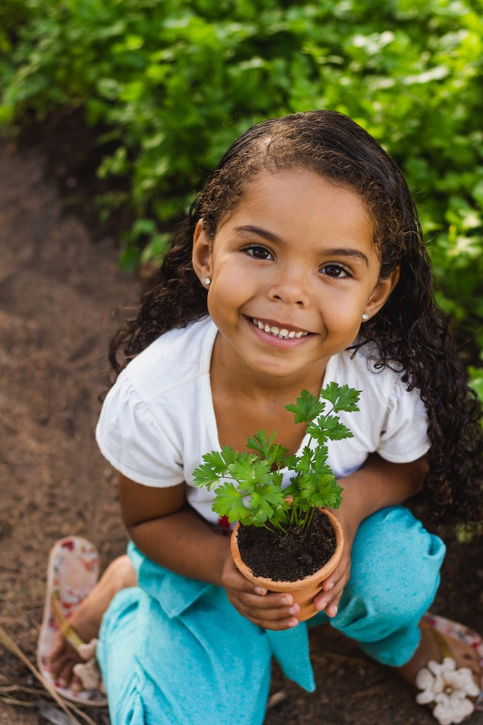 A young Honduran girl holds a flower pot with a bright green plant growing in it. She is smiling and wearing a white t-shirt.