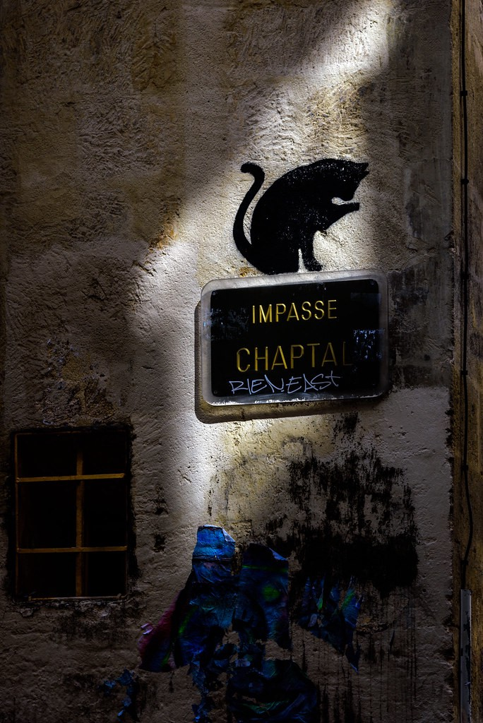 textured wall with a small window and graffiti. On the wall is a sign that reads impasse chapta and a spray painted black cat