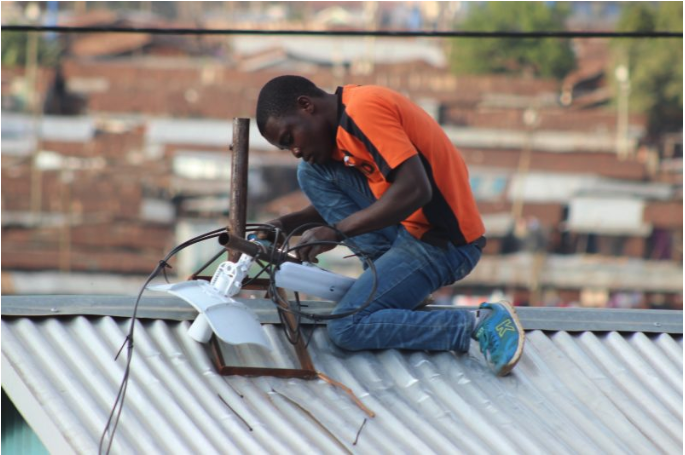 In the urban slums of Kenya, a man installs a networking equipment on the roof of a building.