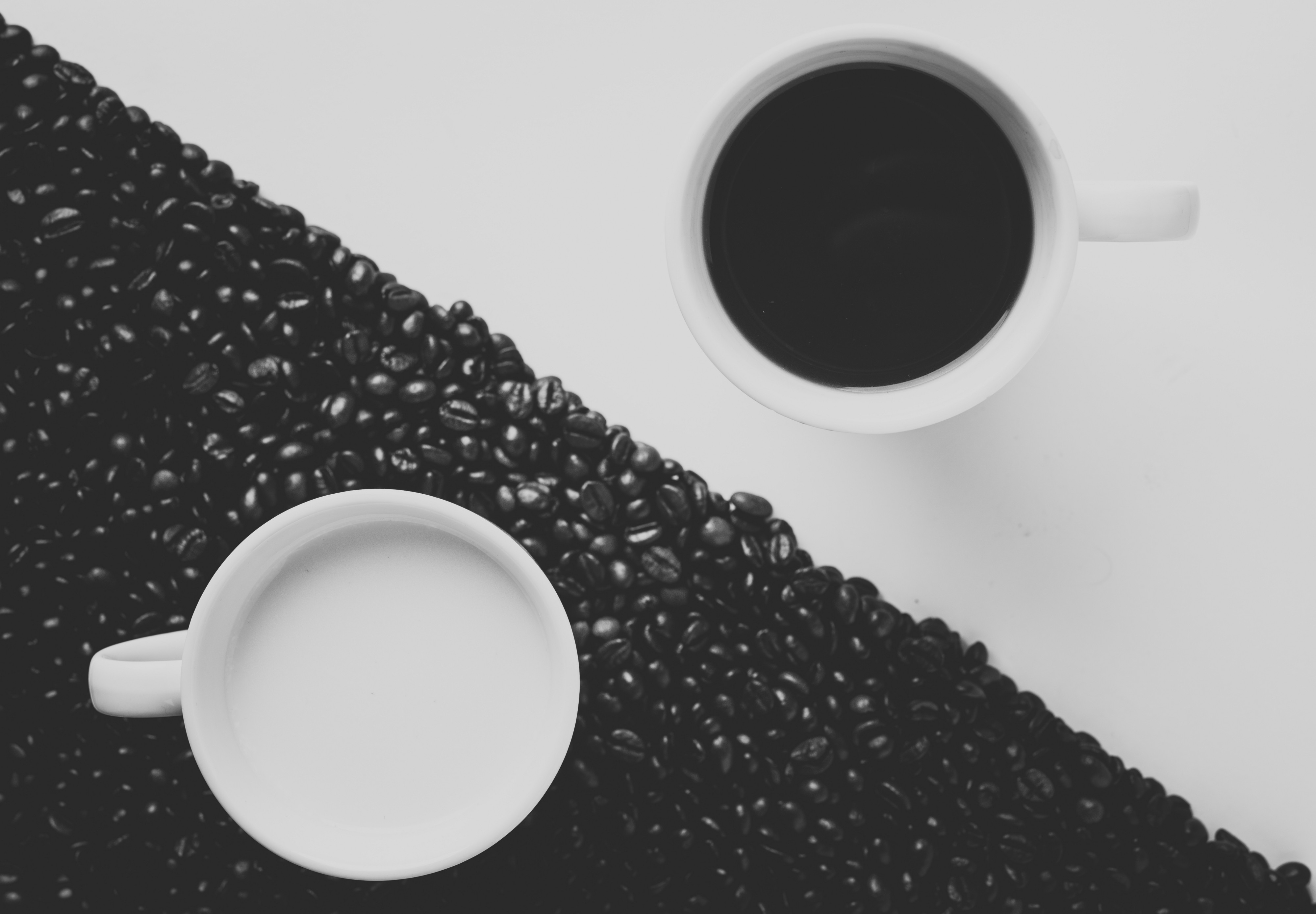 Coffee and milk on a table, with one half of the table covered in coffee beans.