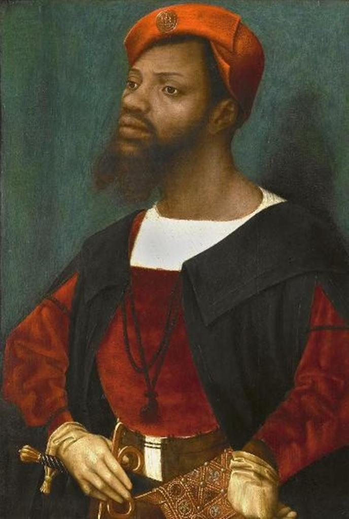 A Black man shown from the waist up wearing an expensive & fashionable red & black outfit with a detailed tooled sword belt.