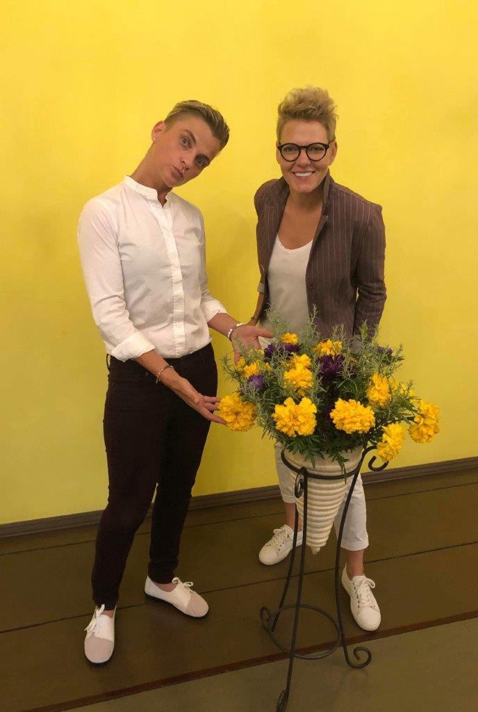 Inga and Evija stand in front of a yellow wall and gesture towards yellow flowers.
