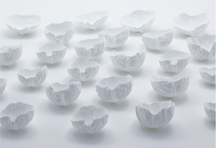 24 white porcelin bowls on a white table top. Each bowl is in the shape of a slightly different cupped cabbage leaf.
