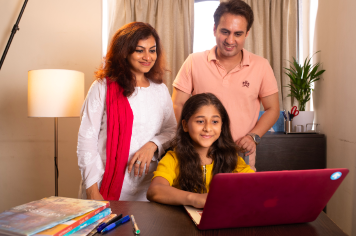 Smiling mom, dad and daughter looking into the laptop, kept on wooden table with a plant and a floor lamp in the background.