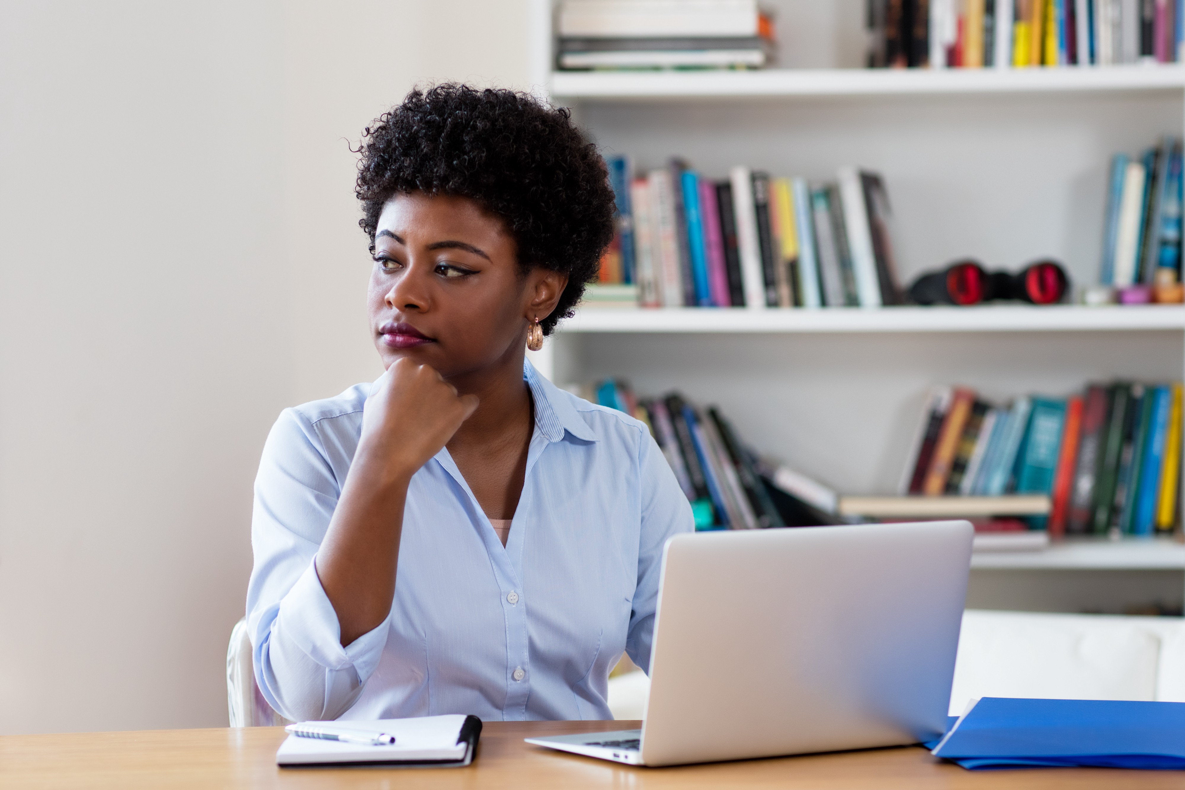 An African American businesswoman looking pensive while at home, in front of her laptop.