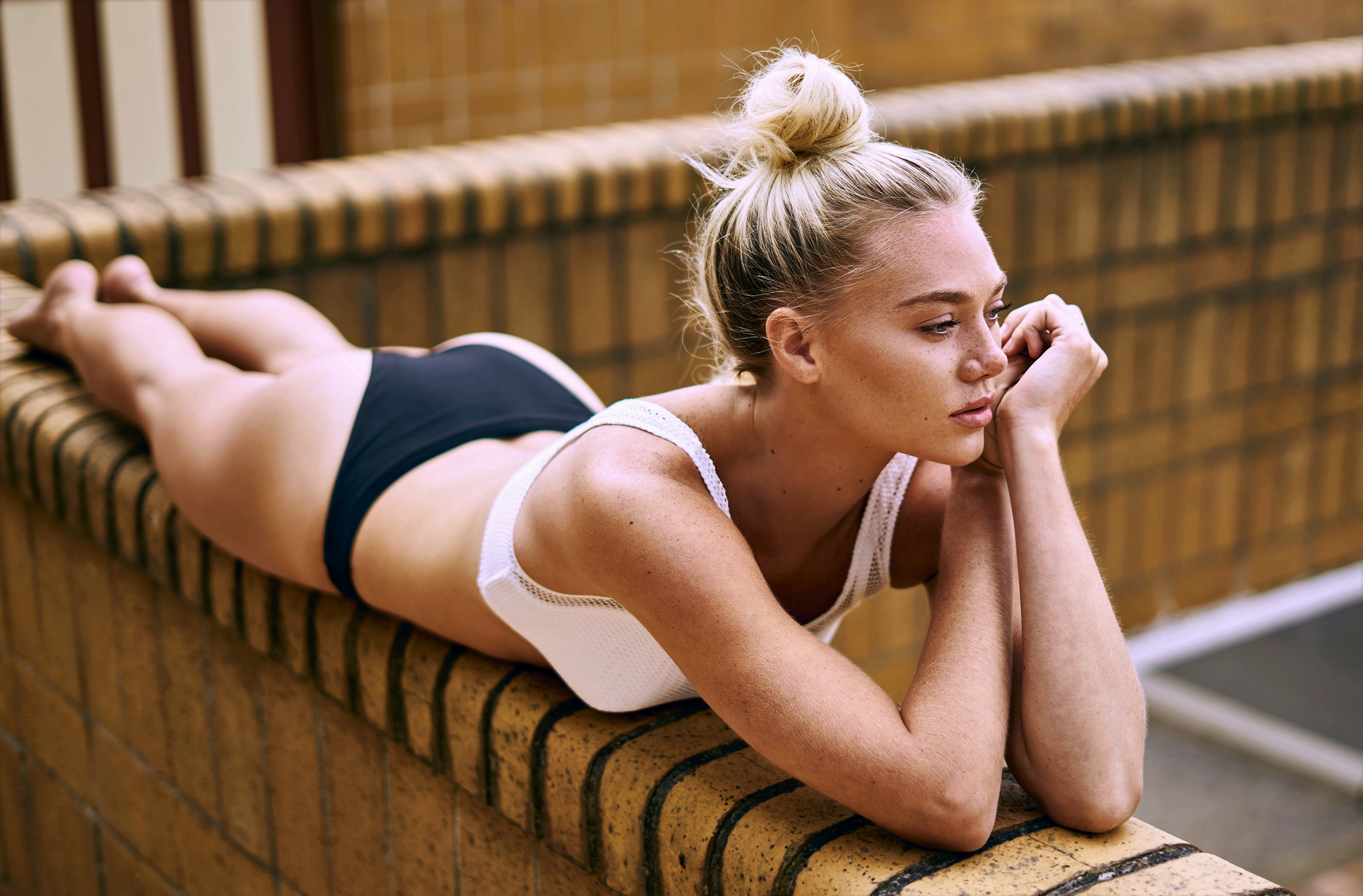 girl with blond hair pulled up wearing white bra and black panties lying on brick wall hands under chin