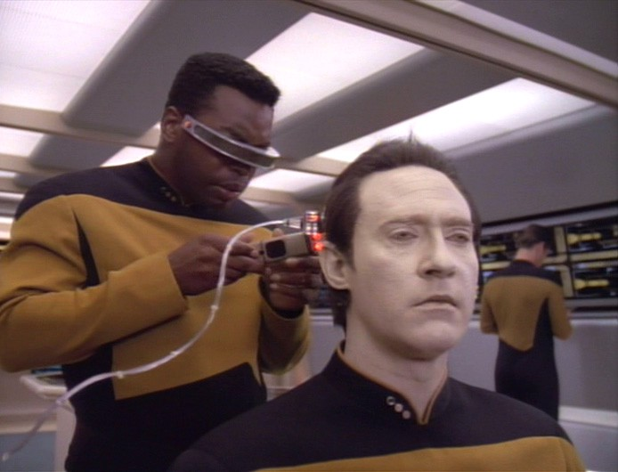 Geordi LaForge doing diagnostics on Data on Star Trek