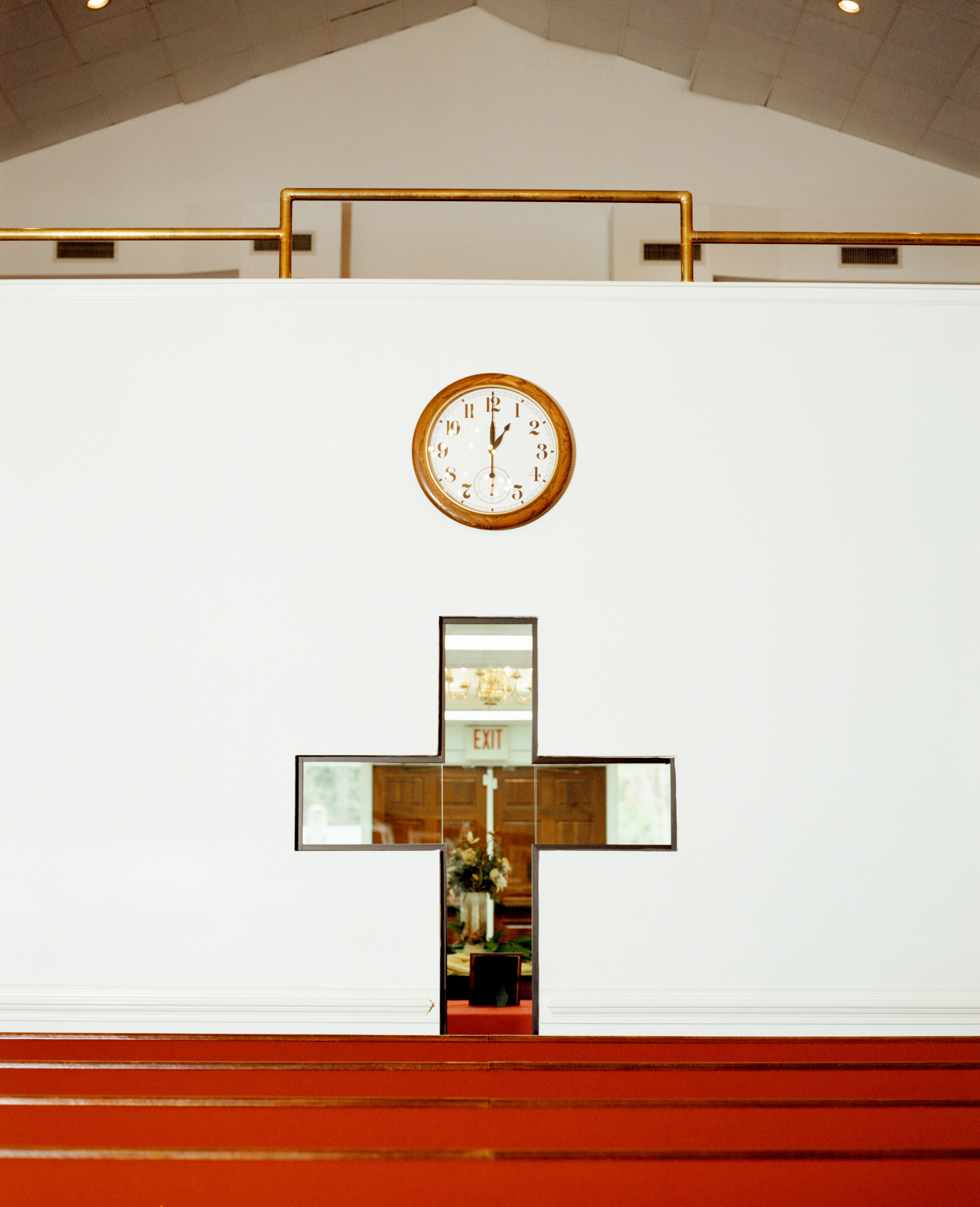 A cross shaped mirror hangs on the wall below a clock at the New Nation Ministry in Columbia, South Carolina.